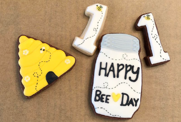Image of sugar cookies in the shape of a beehive, a Mason jar, and a number 1.
