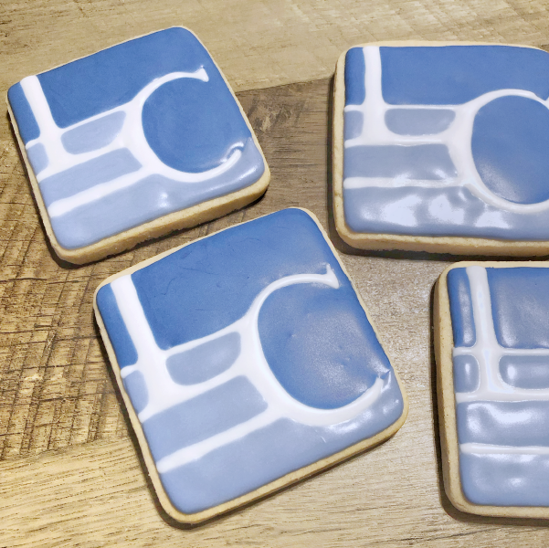 Image of vanila sugar cookie with a blue and white company logo piped on them.