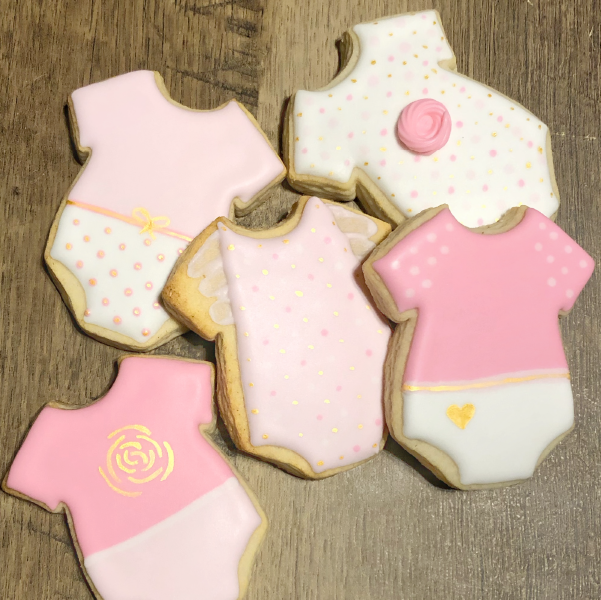 Image of vanilla sugar cookies in the shape of a baby's onesie painted pink.